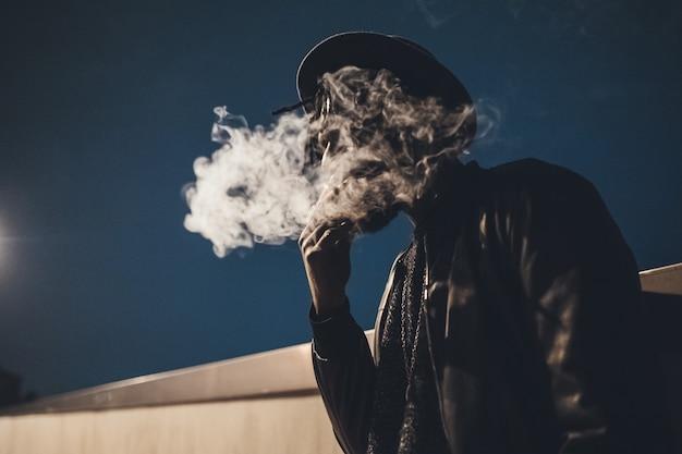Retrato, de, jovem, homem preto, ficar, cigarro ao ar livre, fumar Foto Premium