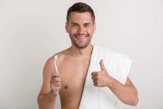Retrato, de, jovem, homem sorridente, mostrando, polegar cima, gesto, enquanto, segurando, escova dente Foto gratuita