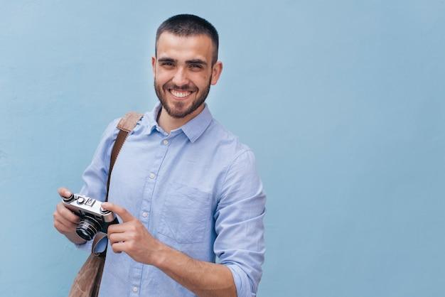 Retrato, de, jovem, homem sorridente, segurando, câmera está pé, contra, parede azul Foto gratuita