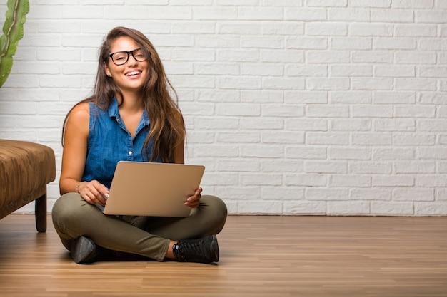 Retrato, de, jovem, latim, mulher senta-se chão, alegre, e, com, um, grande sorriso Foto Premium