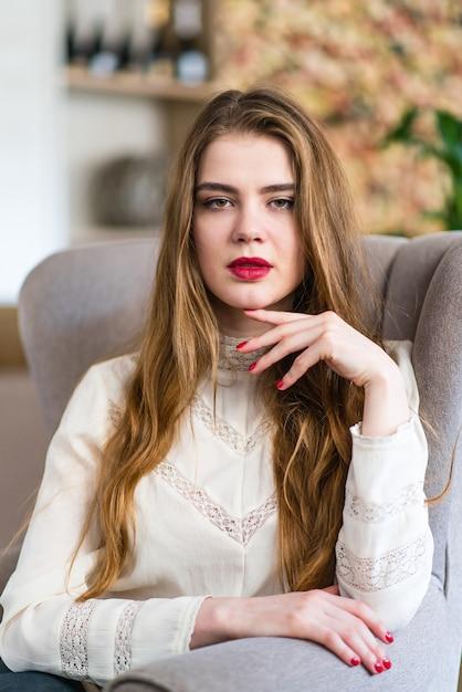 Retrato de jovem linda com maquiagem profissional e penteado no restaurante. Foto Premium