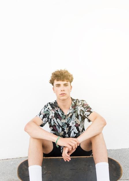 Retrato, de, jovem, macho, skateboarder, sentando, contra, branca, parede Foto gratuita