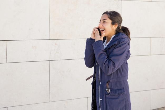Retrato, de, jovem, mulher asiática, fofoque, ligado, telefone móvel, ao ar livre Foto gratuita