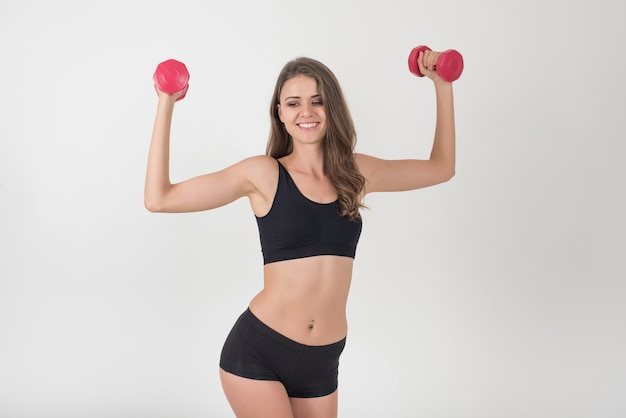 Retrato, de, jovem, mulher bonita, fazer, exercícios físicos, com, dumbbells Foto gratuita