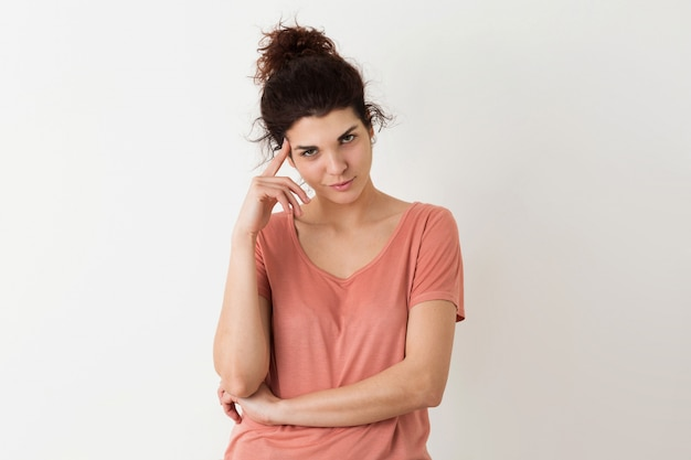 Retrato de jovem natural olhando sorrindo feliz mulher bonita hipster em camisa rosa posando isolado, pensando e tendo um problema Foto gratuita