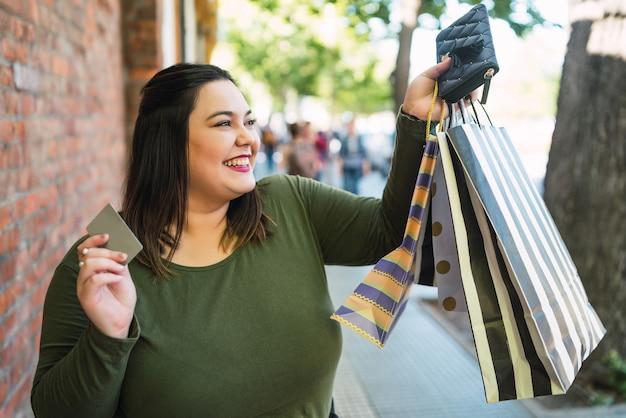 Retrato de jovem plus size mulher segurando um cartão de crédito e sacolas de compras ao ar livre na rua. conceito de compra e venda. Foto gratuita