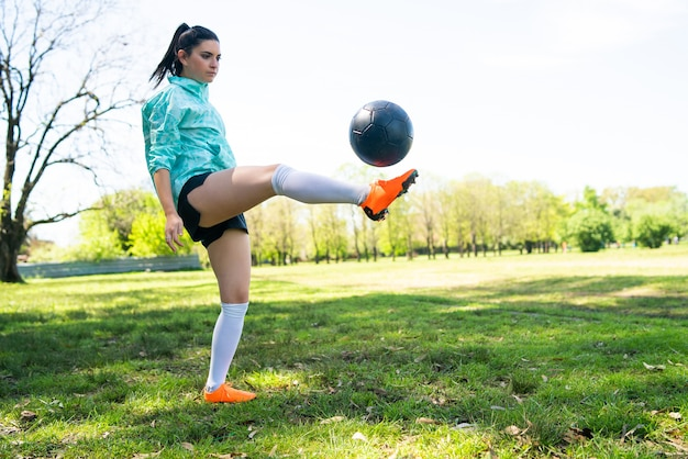 Retrato de jovem praticando futebol e fazendo manobras com a bola de futebol Foto gratuita