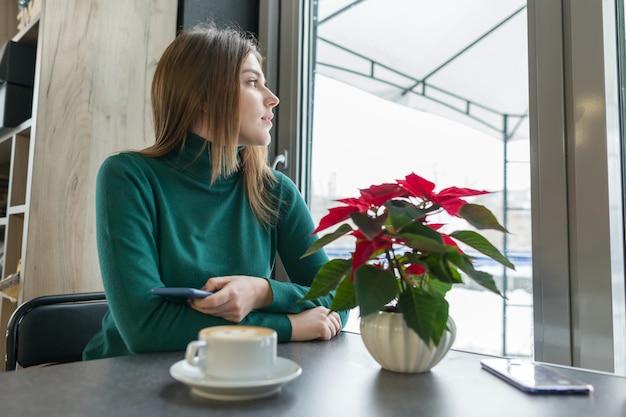 Retrato de jovem rapariga bonita sentada no café Foto Premium