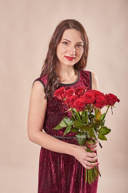 Retrato de jovem satisfeito vestido vermelho com buquê de rosas Foto Premium