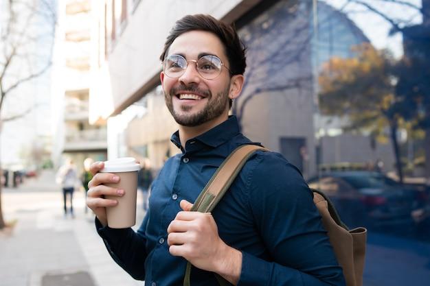 Retrato de jovem segurando uma xícara de café enquanto caminhava ao ar livre na rua. conceito urbano e de estilo de vida. Foto gratuita