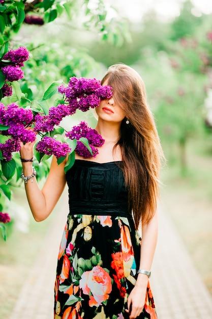 Retrato de jovem sensual com cabelos longos, desfrutando de anf relaxante no parque florescendo primavera. Foto Premium
