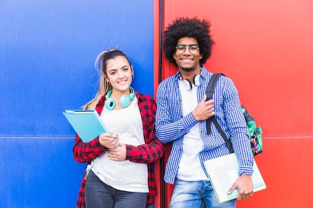 Retrato, de, jovem, sorrindo, par adolescente, segurando, livros, ficar, contra, vermelho azul, parede Foto gratuita