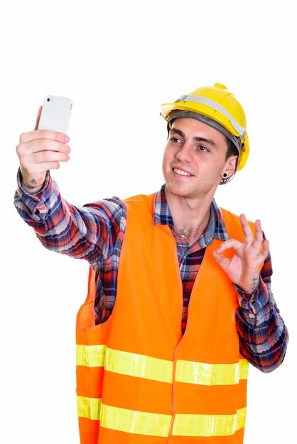 Retrato de jovem trabalhador da construção civil tomando selfie Foto Premium