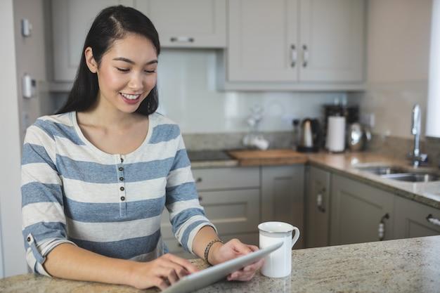 Retrato de jovem usando um tablet digital na cozinha Foto Premium