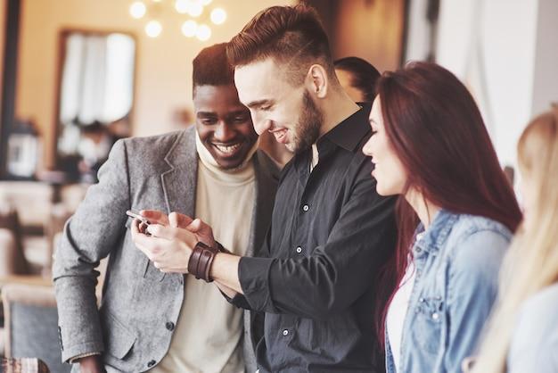 Retrato de jovens amigos alegres, olhando para o telefone inteligente enquanto está sentado no café Foto Premium