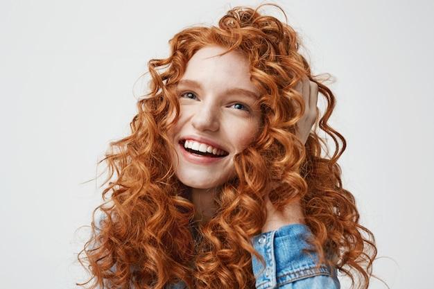 Retrato de linda garota feliz sorrindo tocando seu cabelo ruivo cacheado. Foto gratuita