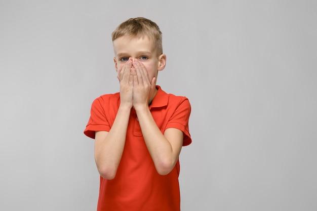 Retrato de loiro menino triste caucasiano em camiseta laranja, fechando a boca com as mãos no fundo cinza Foto Premium