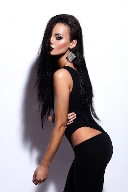 Retrato de look.glamor de alta moda modelo sexy caucasiano elegante morena jovem bonita com lábios pretos, maquiagem brilhante, com pele molhada limpa perfeita em pano preto Foto gratuita