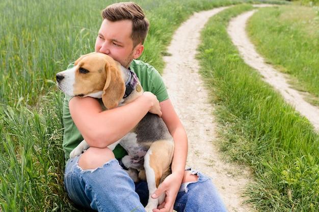 Retrato de macho adulto segurando beagle bonito Foto gratuita