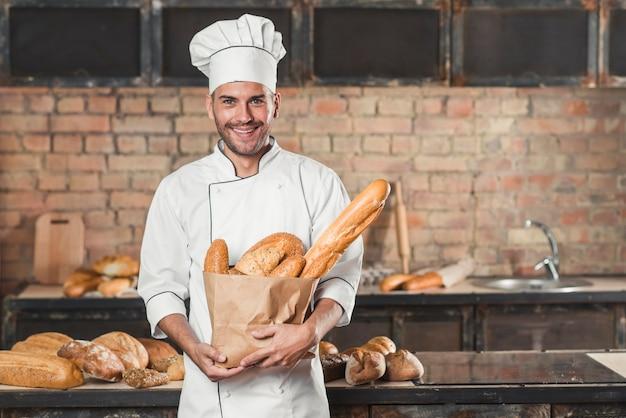 Retrato, de, macho, padeiro, segurando, loaf, de, pães, em, sacola papel Foto gratuita