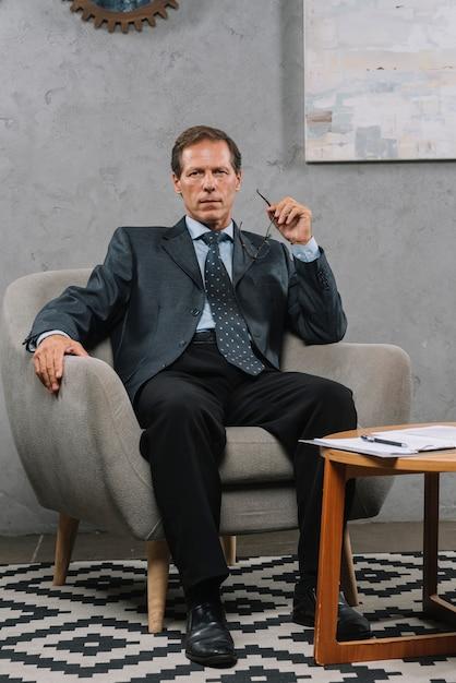 Retrato, de, maduras, homem negócios, sentando, ligado, cozy, poltrona Foto gratuita