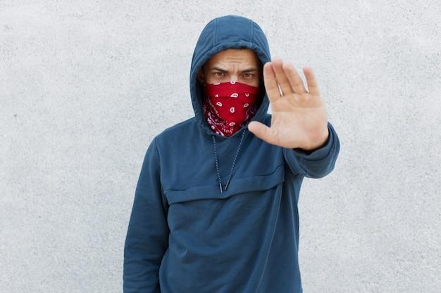 Retrato de manifestante decepcionado grave contra a ilegalidade de cidadãos negros, cara mostrando o gesto de parada com a palma da mão, parar de assassinar pessoas, ativista usando jumper com máscara de capuz e bandana. Foto gratuita