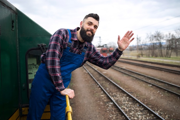 Retrato de maquinista de trem ou locomotiva acenando na estação Foto gratuita
