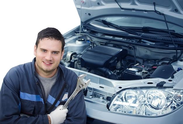 Retrato de mecânico de automóveis bonito profissional segurando chaves na frente do automóvel com o capô aberto. Foto Premium