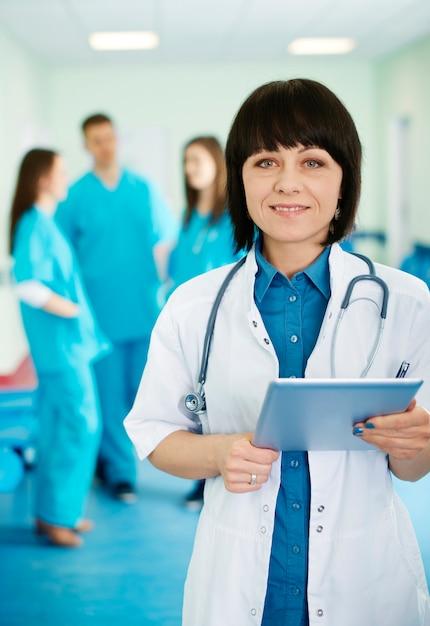 Retrato de médica com estagiários em segundo plano Foto gratuita