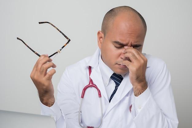 Retrato de médico asiático esfregando os olhos com estetoscópio Foto Premium