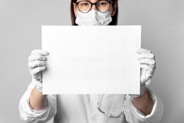 Retrato de médico com máscara cirúrgica segurando um cartaz Foto Premium