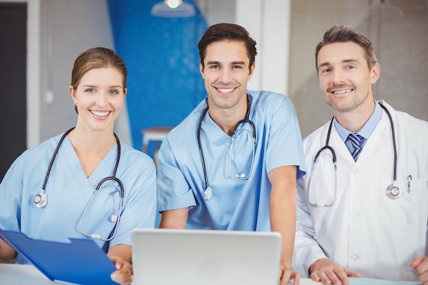 Retrato de médicos alegres com laptop e área de transferência Foto Premium
