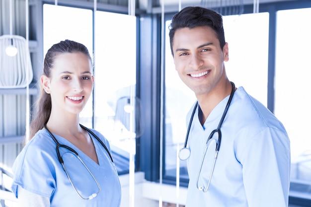 Retrato de médicos juntos e sorrindo para a câmera no hospital Foto Premium