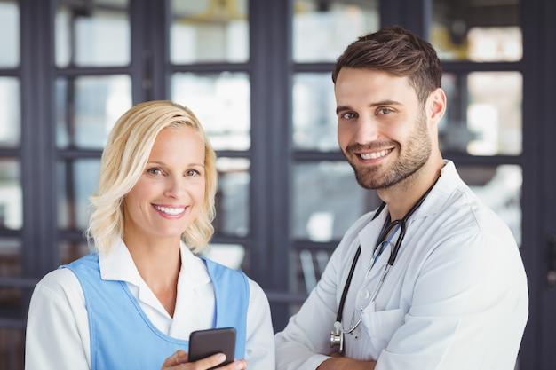 Retrato de médicos sorridentes usando telefone celular Foto Premium