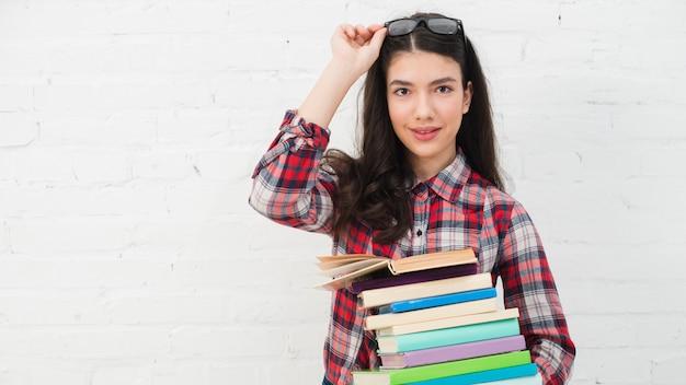 Retrato, de, menina adolescente, com, pilha livros Foto gratuita