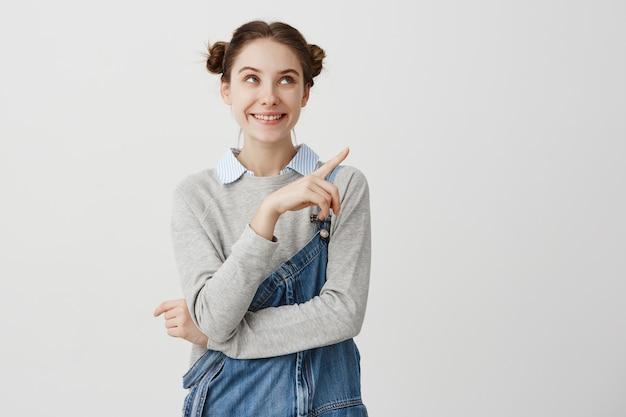Retrato de menina adulta muito positivo com pães duplos, apontando o dedo. jovem arquiteto feminino com dignidade, demonstrando seu trabalho na parede branca. copie o espaço Foto gratuita