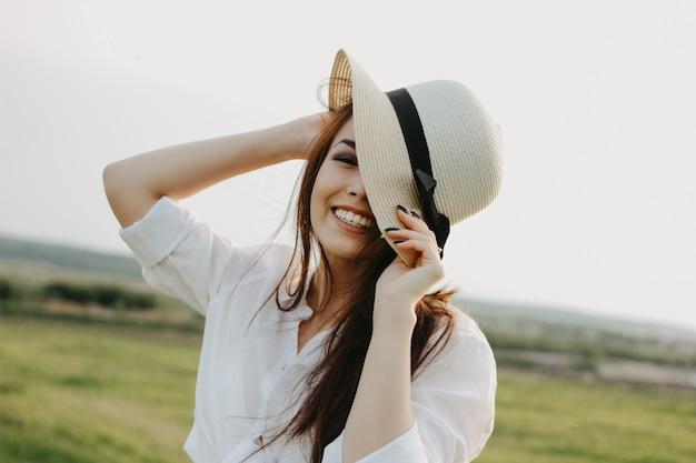Retrato de menina asiática de cabelo comprido despreocupado bonito em roupas brancas e chapéu de palha aprecia a vida no campo da natureza Foto Premium
