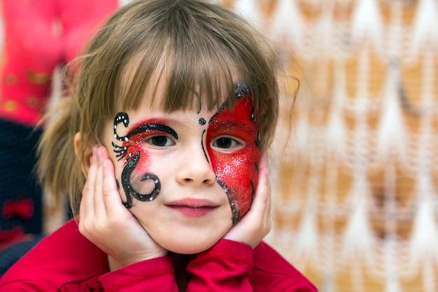 Retrato de menina bonita com pintura de borboleta no rosto Foto Premium