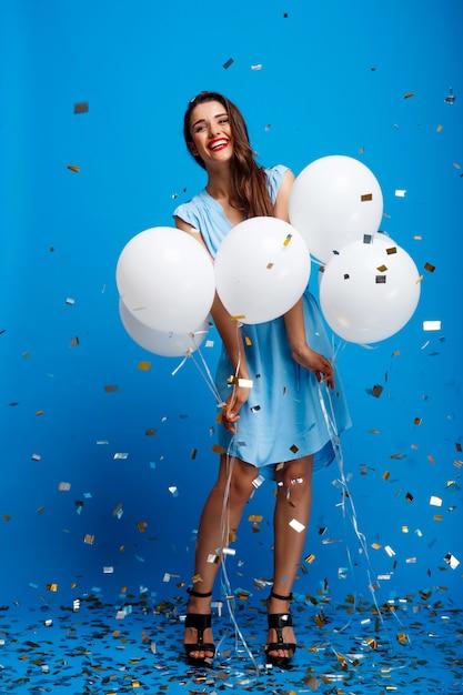 Retrato de menina bonita, descansando na festa sobre parede azul Foto gratuita