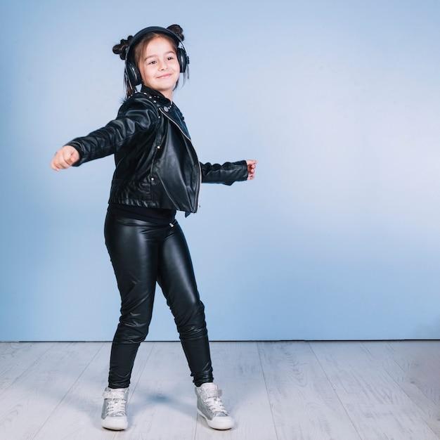 Retrato, de, menina bonita, desgastar, elegante, roupa preta, dançar, contra, parede azul Foto gratuita