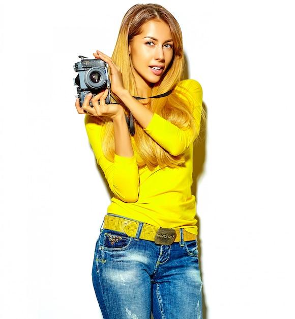 Retrato de menina bonita feliz sorridente mulher loira bonita com roupas de verão casual tira fotos segurando a câmera fotográfica retrô, isolada em um branco Foto gratuita