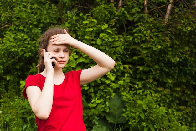 Retrato de menina bonita preocupada falando no celular no parque Foto gratuita