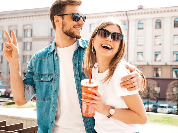 Retrato de menina bonita sorridente e seu namorado bonitão em roupas de verão casual. . com garrafa de água e palha Foto gratuita