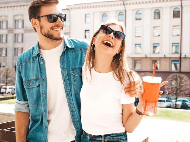 Retrato de menina bonita sorridente e seu namorado bonitão em roupas de verão casual. . mulher com garrafa de água e palha Foto gratuita