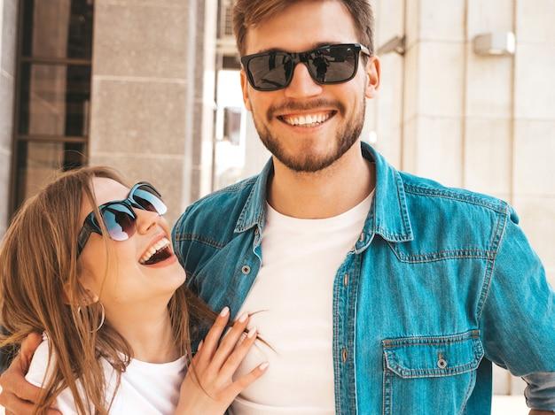 Retrato de menina bonita sorridente e seu namorado bonito em roupas de verão casual e óculos de sol. . abraçando Foto gratuita