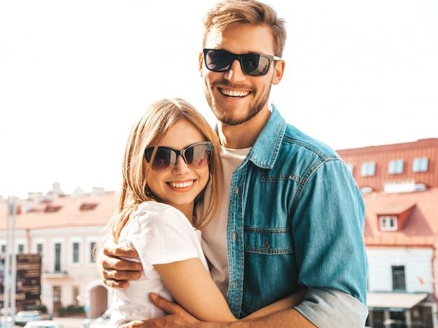 Retrato de menina bonita sorridente e seu namorado bonito em roupas de verão casual e óculos de sol. Foto gratuita