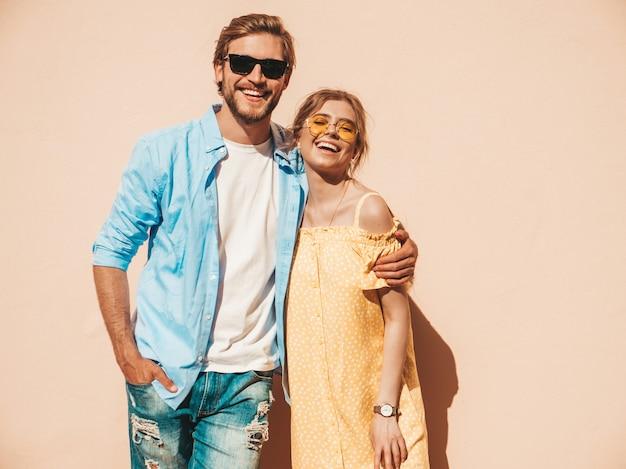 Retrato de menina bonita sorridente e seu namorado bonito. mulher de vestido casual de verão e homem de jeans. família feliz e alegre. fêmea se divertindo na rua perto da parede Foto gratuita