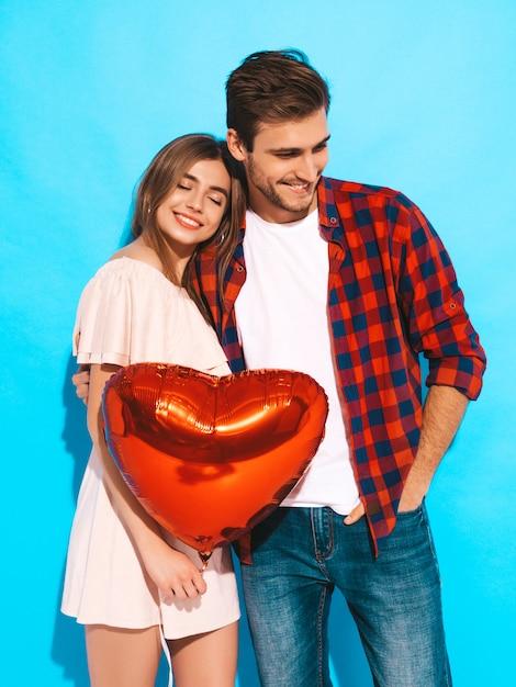 Retrato de menina bonita sorridente e seu namorado bonito segurando balões em forma de coração e rindo. casal feliz no amor. feliz dia dos namorados Foto gratuita