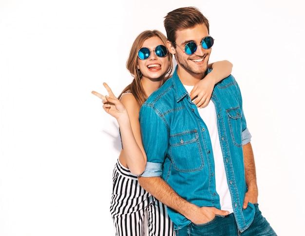 Retrato de menina bonita sorridente e seu namorado considerável rindo. casal alegre feliz em óculos de sol. e mostrando sinal de paz Foto gratuita