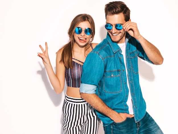 Retrato de menina bonita sorridente e seu namorado considerável rindo. casal alegre feliz em óculos de sol. Foto gratuita